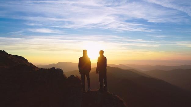 美しい日の出を背景に山に立っているカップル