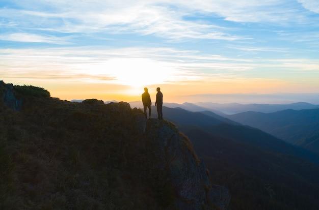 日の出の背景に山に立っているカップル