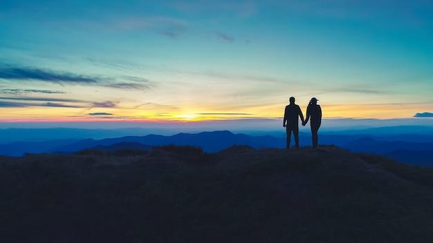 夕日を背景に山に立っているカップル