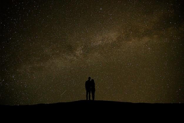 별 배경으로 하늘에 서 있는 커플