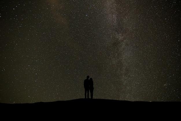 별이 빛나는 하늘 배경에 서있는 커플