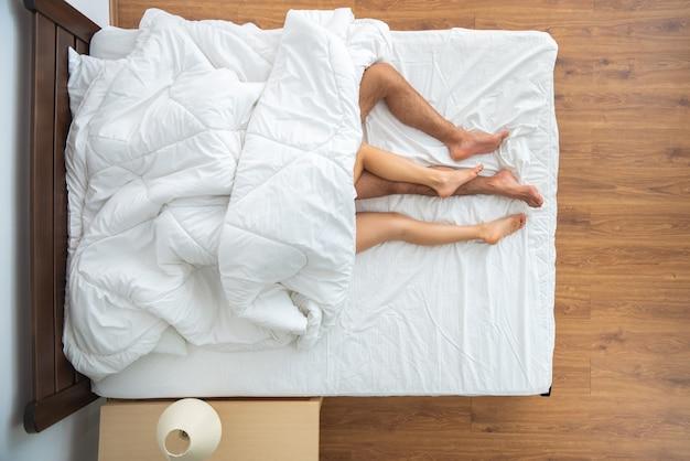 ベッドに横たわっている羽毛布団の下のカップル。上からの眺め