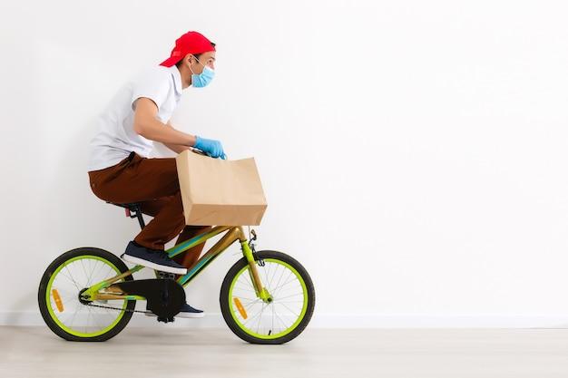 Курьер доставляет коробку с едой во время пандемии коронавируса, горизонтальная ориентация.