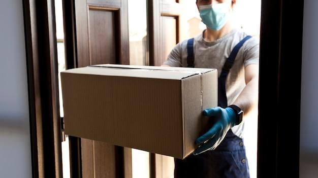 Курьер доставляет домой картонную коробку в латексных перчатках и медицинской маске