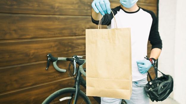 Курьер на велосипеде доставляет бумажный пакет с заказом человеку.