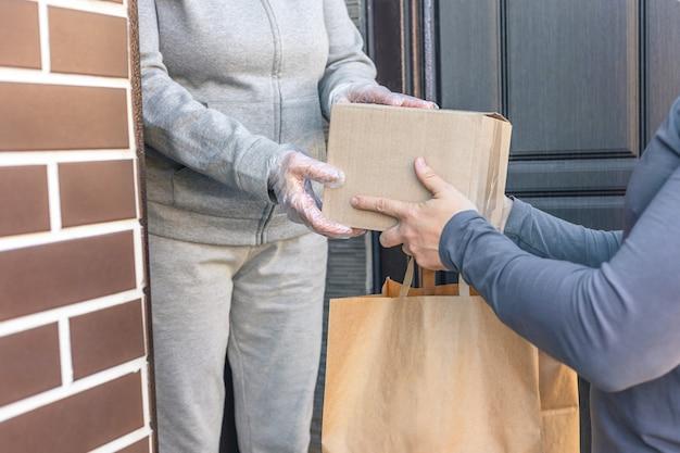 택배는 집에 있는 여성에게 상자를 전달합니다. 배달 서비스. 상자 클로즈업으로 손