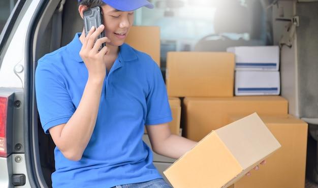 宅配便業者は車の中に座って、電話を使って顧客に連絡しました。
