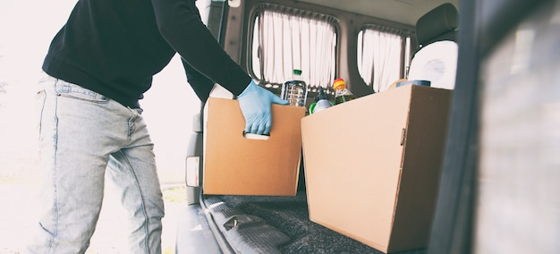 Курьер достает из фургона картонную эко-коробку с продуктами из продуктового магазина.