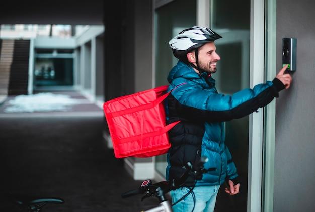 自転車を持った宅配便が家の呼び鈴を鳴らして食べ物を届けます。温かい料理、宅配、ベルを鳴らします。