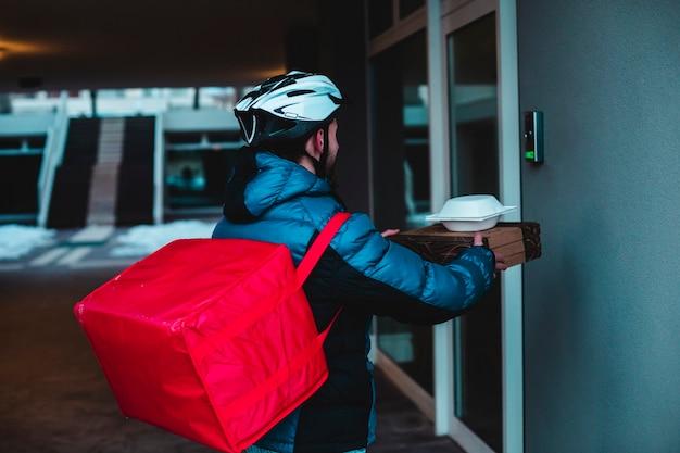 自転車を持った宅配便業者が家のドアベルを鳴らしてピザを配達します。テイクアウトピザ、宅配、ベル音。