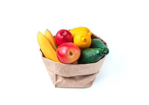 공예 가방은 흰색 바탕에 바나나, 아보카도, 레몬, 사과 등 과일로 가득 차 있습니다. 측면보기. 식품의 개념.