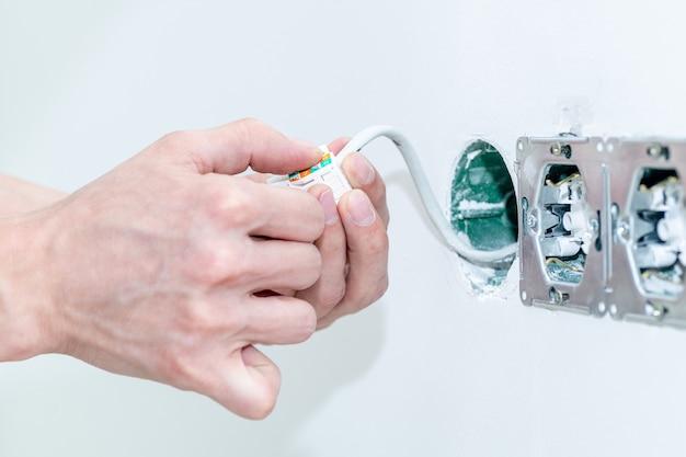Мастер встраивает в стену электрическую розетку. монтаж розетки с соблюдением техники безопасности. крупный план. выборочный фокус.