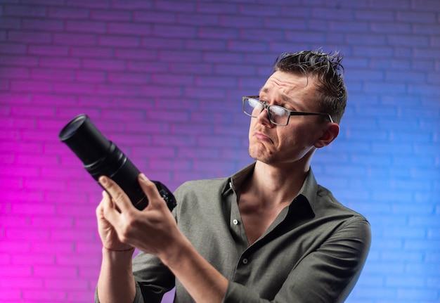 明るいネオンの背景にデジタルカメラとメガネの狂った男