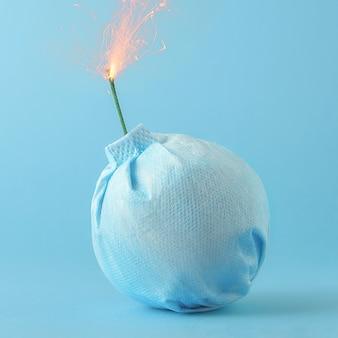 코로나 바이러스 전염병의 창의적인 개념. 파란색 배경에 폭탄의 형태로 의료 마스크.