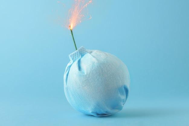 コロナウイルスの流行の創造的な概念。青い背景に爆弾の形で医療マスク。