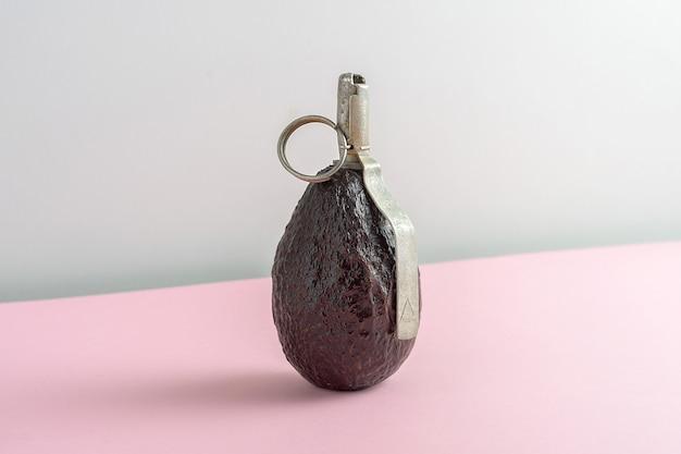 ダイエットの創造的なコンセプト。グレーピンクの背景に手榴弾の形をしたアボカド。