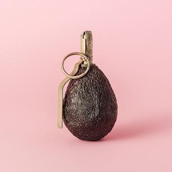 ダイエットの創造的なコンセプト。ピンクの背景に手榴弾の形をしたアボカド。