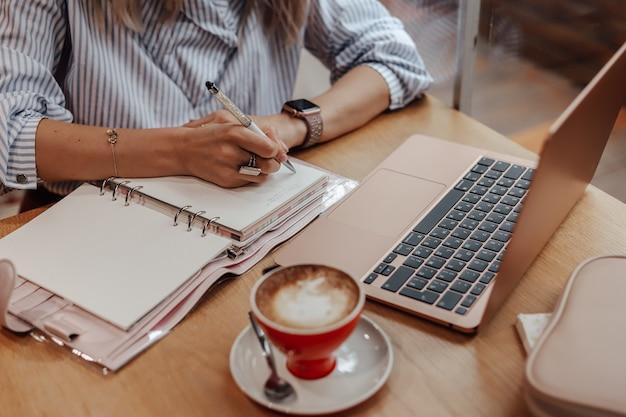 Обрезанная девочка работает, делает записи в ежедневнике.