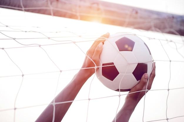 Обрезанное изображение спортивных игроков, которые ловят мяч и футбольное поле. спортивно-имиджевая концепция.
