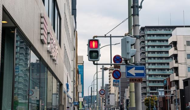 교차 신호등은 도시 거리에서 보행자를 위해 빨간색으로 켜져 있습니다. 교토에서 길을 건너는 것을 금지하는 일본 신호. 일본에서 걷지 마십시오 기호