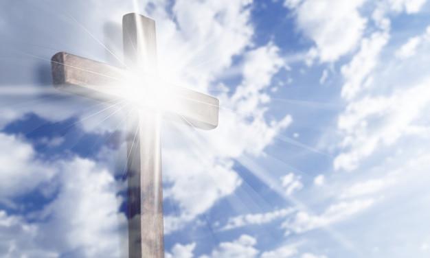 밝은 태양과 구름이 배경에 있는 십자가