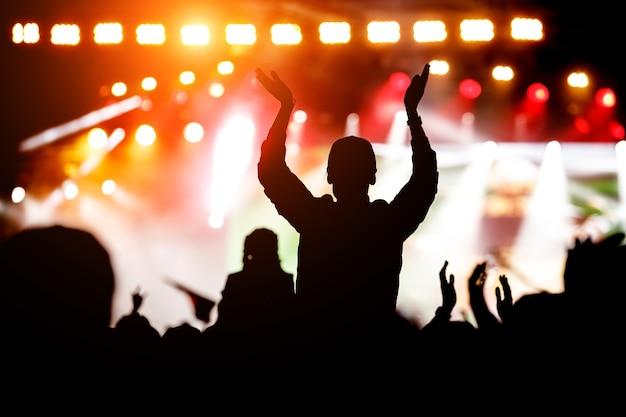 Толпа наслаждается музыкальным шоу. черный силуэт.