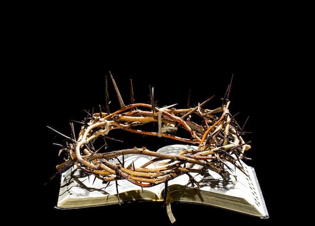 いばらの冠は暗闇の中で聖書の本の上にあります。聖週間の概念とイエスのはりつけ。