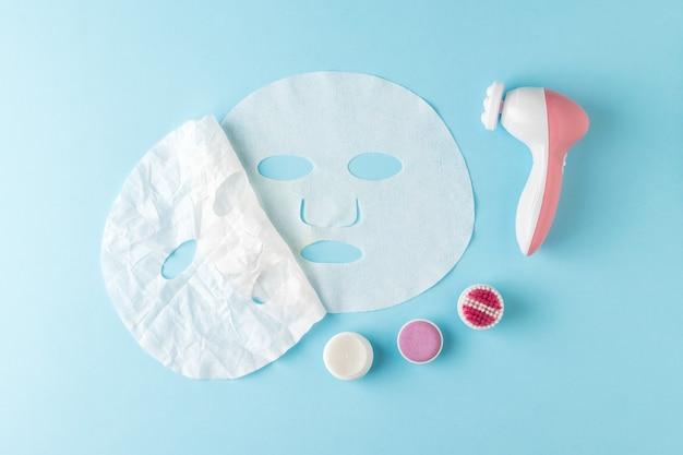 Мятая маска снимается с разглаженной на синем фоне и массажером. концепция омолаживающего воздействия на кожу.