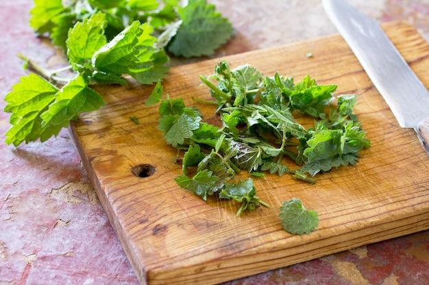 Из измельченных листьев варилась сырая крапива на кухонном столе.