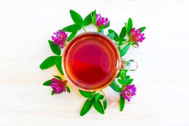 木製のテーブルに赤いクローバーの花と黒のハーブティーのカップ