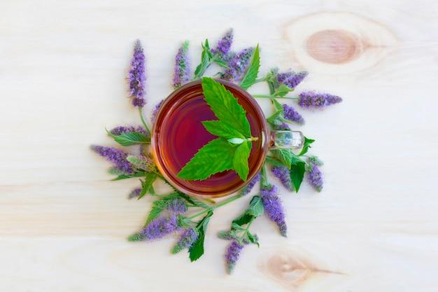 木製のテーブルにミントとミントの花の枝と紅茶のカップ
