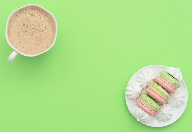 カプチーノと白いメレンゲのおいしいマカロンのカップ。フラットレイスタイル
