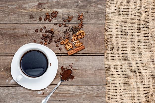 コーヒー豆、ナッツ、シナモンスティックと木製のテーブルの上のコーヒーのカップ