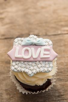 Кекс со словом любовь на коричневом фоне. день святого валентина