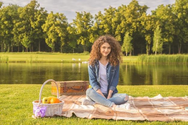 巻き毛の女性は川の近くのピクニックで休む