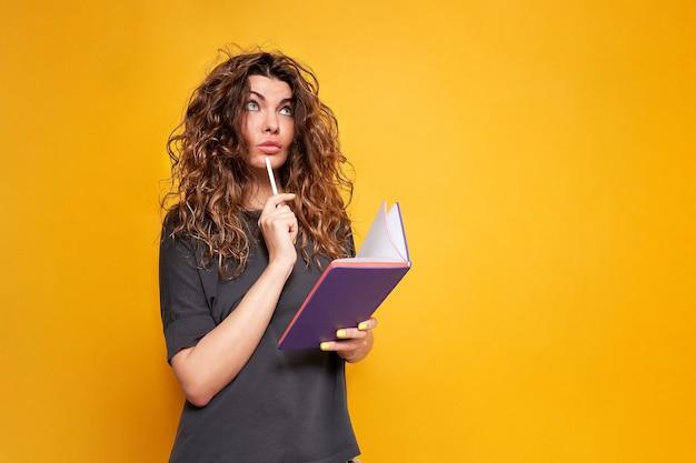 Кудрявая женщина с фиолетовым дневником и белым карандашом