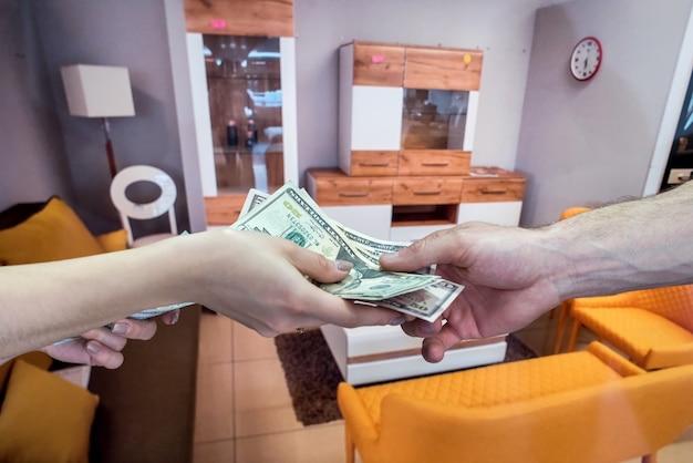 고객은 상점에서 새 가구를 구입하고 판매자에게 달러를 제공합니다.