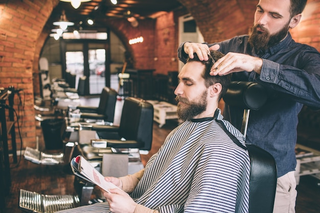 Клиент сидит в кресле и читает журнал, а парикмахер подстригает часть волос. он делает это довольно профессионально.