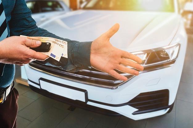 고객은 그의 꿈의 새 차에 대해 유로 지폐를 지불합니다.