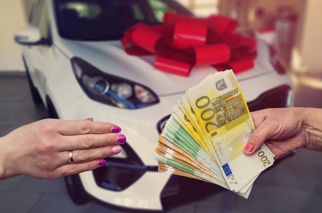 고객은 그의 꿈인 새 차를 위해 유로 지폐를 지불합니다.