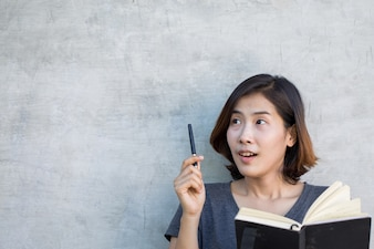 The cute Asian women are thinking something with her book on gray background