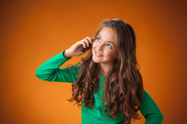 Милая веселая маленькая девочка на оранжевом фоне