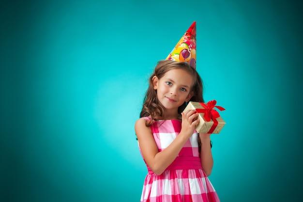 Милая веселая маленькая девочка с подарком и праздничной шапочкой на синем фоне