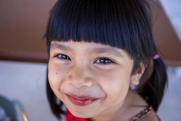Милая маленькая азиатская девочка с удовольствием ест мороженое.