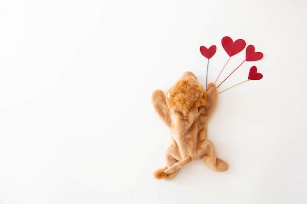 귀여운 작은 사자는 발렌타인 데이에 많은 마음으로 너무 행복합니다.