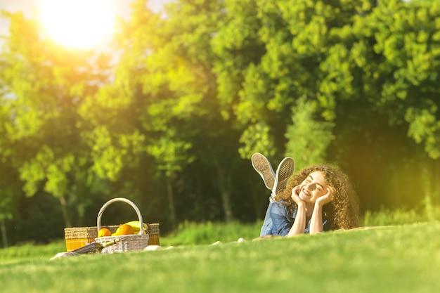 Милая женщина лежала на траве в парке