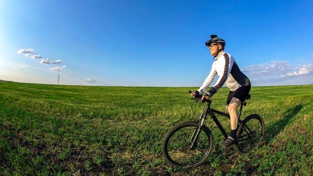 자전거 타는 사람은 들판의 푸른 잔디에서 자전거를 탄다. 야외 운동. 건강한 생활.