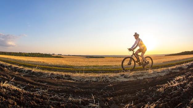 자전거 타는 사람은 석양을 배경으로 들판 근처의 도로에서 자전거를 탄다. 야외 운동. 건강한 생활.