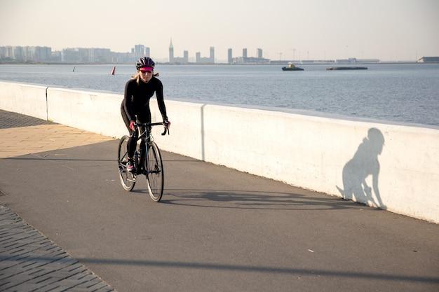 サイクリストは最初の太陽の光で堤防に沿って乗ります