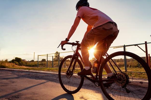 サイクリストは日没時に太陽光線で自転車に乗ります。スポーツ。アクティブなライフスタイルのコンセプト。